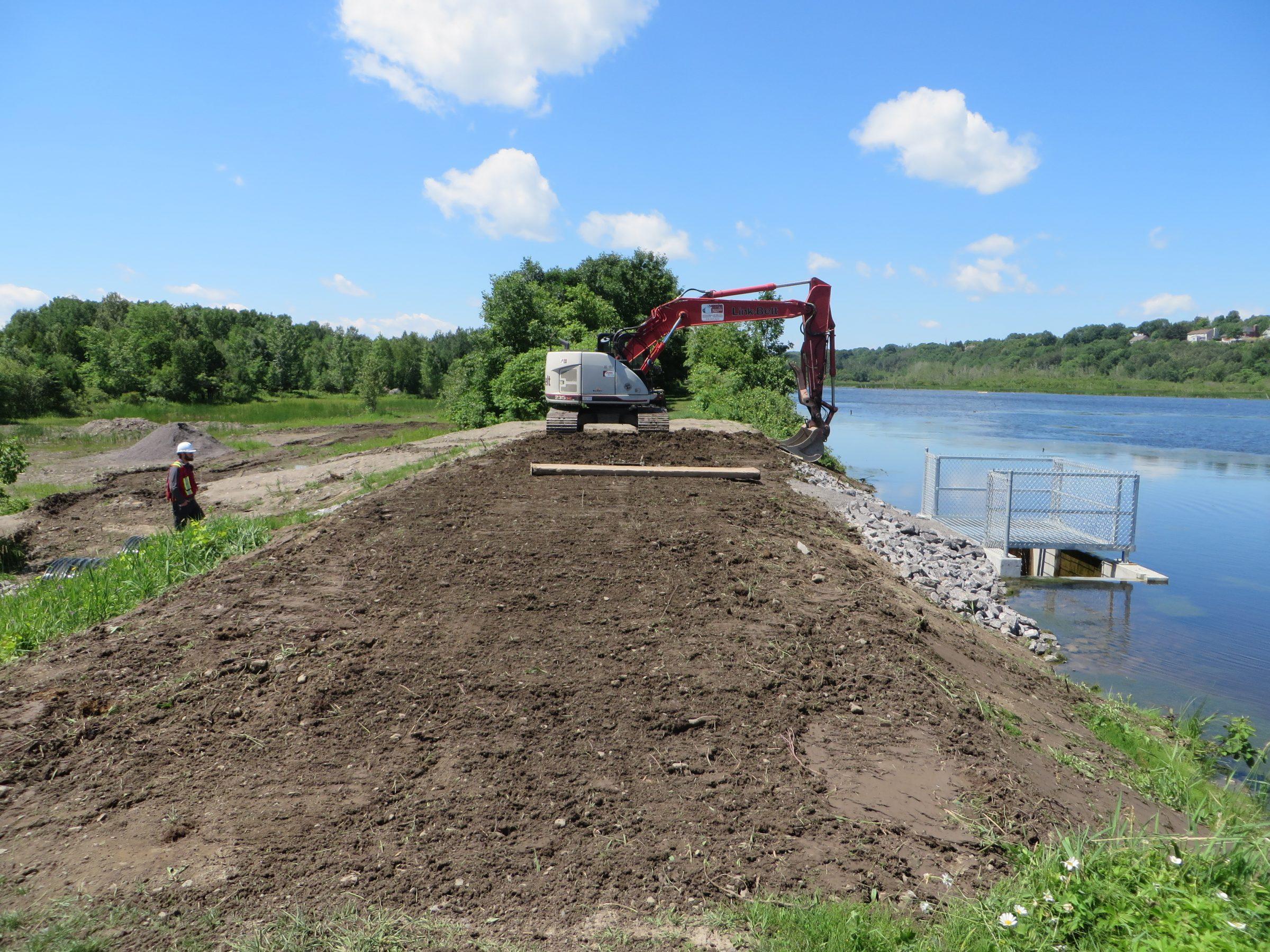 Derniers ajustements à la digue suite au remplacement du barrage à l'exutoire du marais Léon-Provancher. Juillet 2018. Photo : Réhaume Courtois.