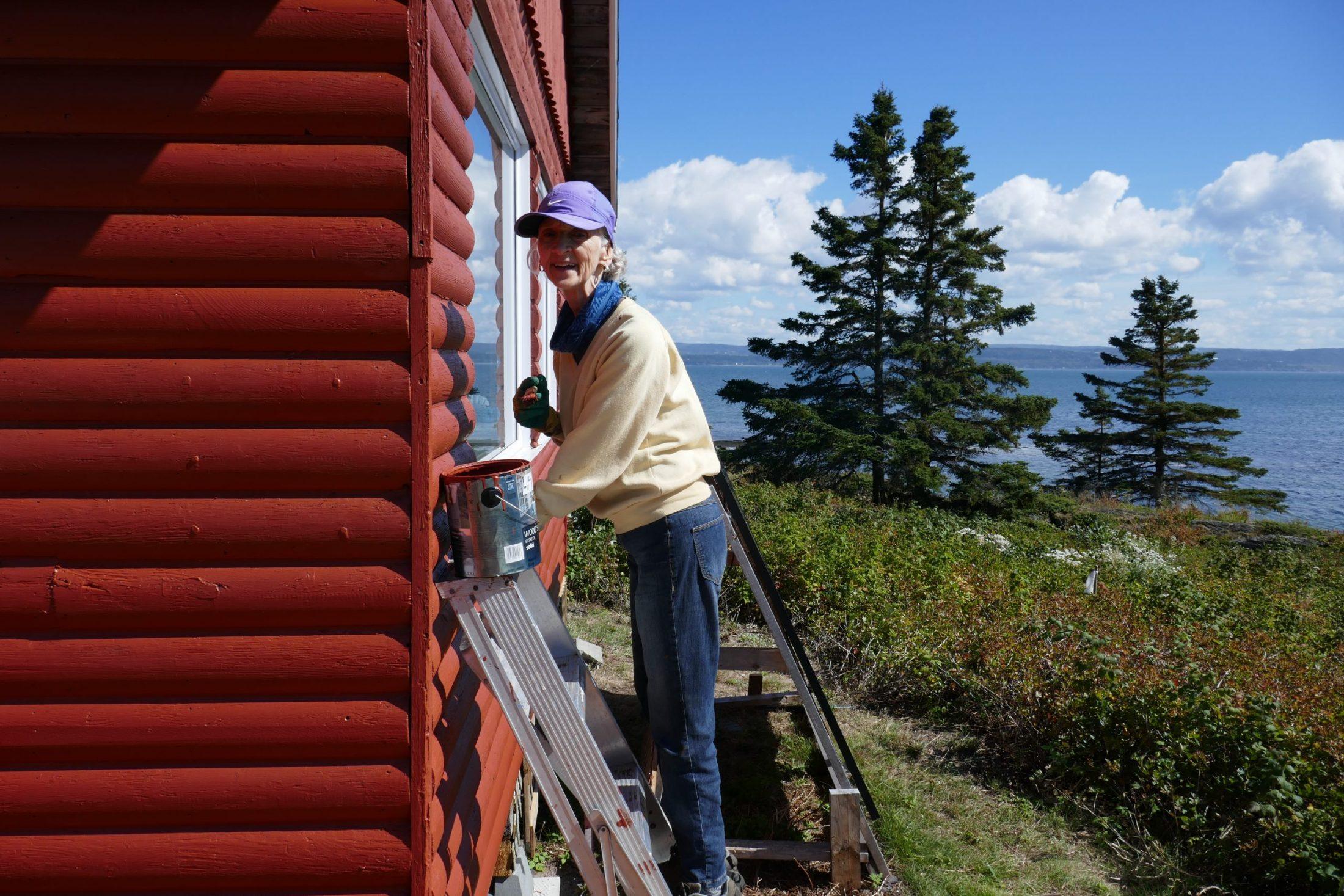 """Corvée de rénovation à l'île aux Basques. Le beau temps aidant, une bévévole, Claire Arsenault, met la dernière """"goutte"""" de peinture au chalet Rex-Meredith, 3 septembre 2020. Photo : Daniel Banville."""