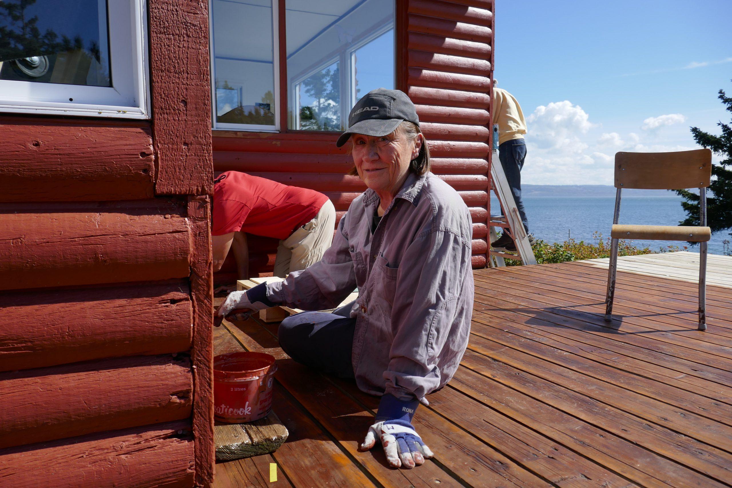 """Corvée de rénovation à l'île aux Basques. Le beau temps aidant, une bévévole, Marianne Kugler, met la dernière """"goutte"""" de peinture au chalet Rex-Meredith, 3 septembre 2020. Photo : Daniel Banville."""